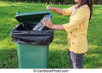 A mano tirando una botella de plástico vacía a la basura