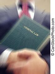 Abogado sosteniendo un libro de derecho criminal