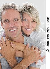 Abrazando a una pareja sonriendo a la cámara