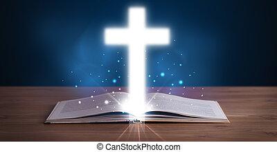 Abre la santa biblia con una cruz resplandeciente en el medio