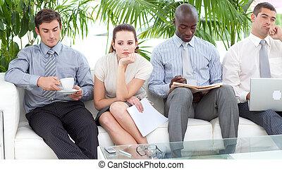 Aburridos empresarios multiétnicos sentados en un sofá esperando una entrevista