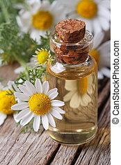 Aceite de manzanilla en una botella de vidrio macro vertical