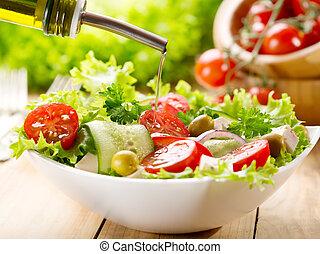 Aceite de oliva derramando sobre ensalada