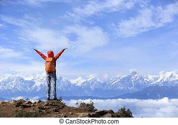 Aclamando a las jóvenes excursionistas abren los brazos a hermosas cumbres de montaña de nieve