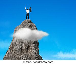 Aclamando en la cima de la montaña rocosa con cielo azul