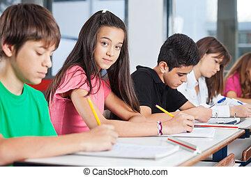 Adolescente sentada con compañeros escribiendo en el escritorio