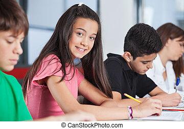 Adolescente sentada con compañeros estudiando en el escritorio