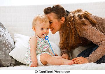 Adorable bebé con soother y joven madre jugando en diván