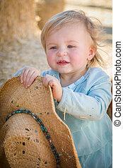 Adorable nena con sombrero vaquero en el campo de calabazas