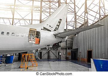 Aeronave en el hangar en mantenimiento de placas, interiores, reparación trasera.