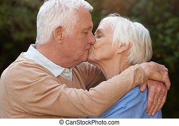 Afectos mayores enamorados abrazando y besando al aire libre