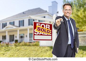 Agente con llaves frente a un letrero y casa vendidos
