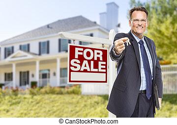 Agente con llaves frente al cartel de venta y la casa