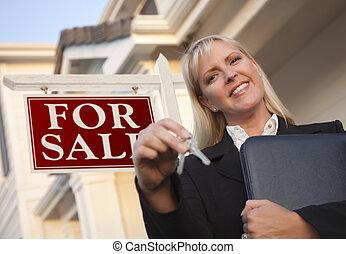 Agente de bienes raíces con llaves en frente del cartel y la casa