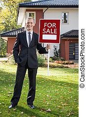 Agente de bienes raíces de pie en frente de la casa