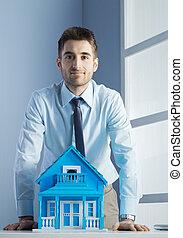 Agente inmobiliario con casa modelo
