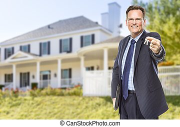 Agente inmobiliario con llaves de casa en frente de casa