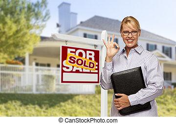 Agente inmobiliario en frente de la firma vendida y la casa