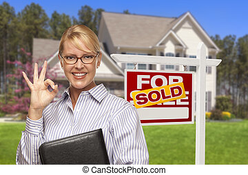 Agente inmobiliario frente a la casa y el cartel vendidos