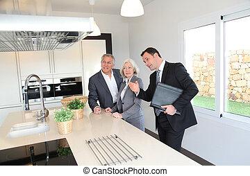 Agente inmobiliario mostrando el interior de la casa a la pareja de ancianos