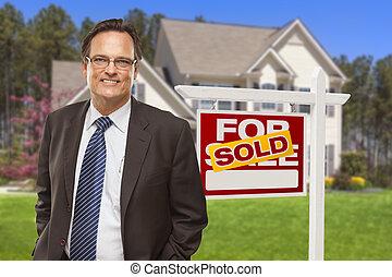 Agentes de bienes raíces masculinos frente a la casa y el cartel vendidos