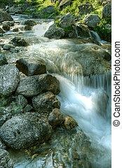 Agua cayendo a través de rocas de montaña