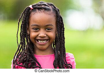 Al aire libre, el retrato de una joven y bonita chica negra sonriente