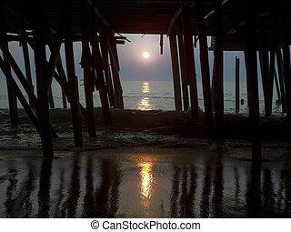 Al amanecer en el viejo muelle del océano