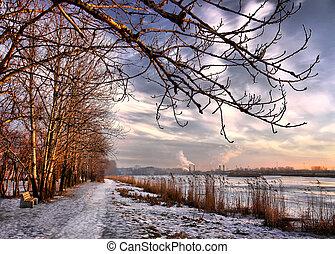 Al atardecer al final del invierno, el lago de la ciudad