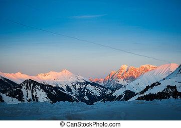 Al atardecer en la montaña de nieve de Tyrol en invierno