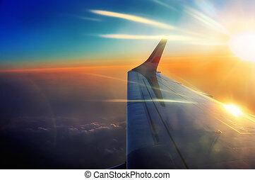 Ala del avión en vuelo en las vigas del amanecer