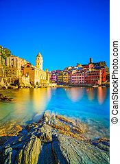 Aldea Vernazza, iglesia, rocas y puerto marítimo en la puesta de sol, marescape en cinco tierras, cinque terre National Park, liguria italy europe. Una larga exposición.