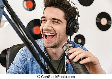 Alegre joven presentador de radio transmitiendo