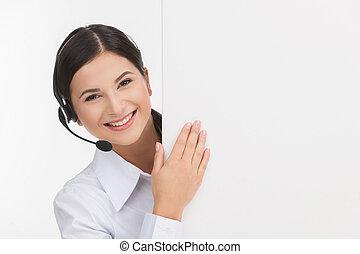 Alegre representante de servicio al cliente. Alegre y joven representante de servicios al cliente en audífonos mirando fuera del cartel mientras está aislado en blanco