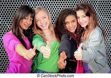 Alegres chicas adolescentes mostrando pulgares hacia arriba
