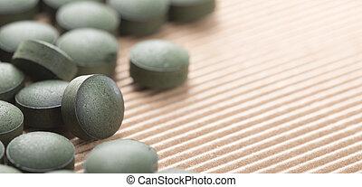 Algas verdes azules. Detalles de tabletas de espirulina artesanales sobre fondo natural.