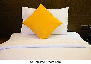 Almohadas amarillas en una cama cómoda