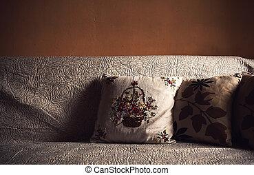 Almohadas decorativas en el sofá viejo