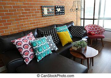 Almohadones coloridos en un sofá con paredes de ladrillo en el fondo