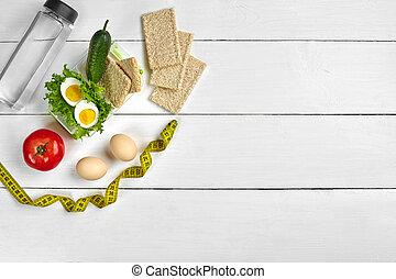 Almuerzo con comida saludable. Huevos, vegetales y una botella de agua sobre fondo blanco de madera. Vista superior con espacio de copia
