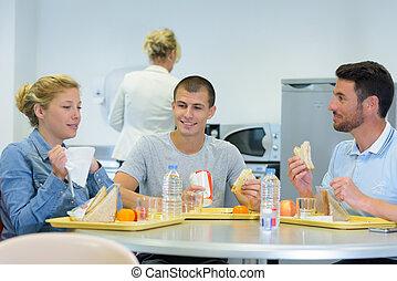 alrededor, sentado, de, adultos, comida, bandejas, empacado, almuerzos, tabla