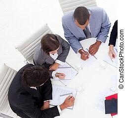 Alto ángulo de un joven empresario internacional discutiendo una nueva estrategia en la oficina