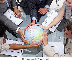 Alto ángulo del equipo de negocios con un globo terrestre