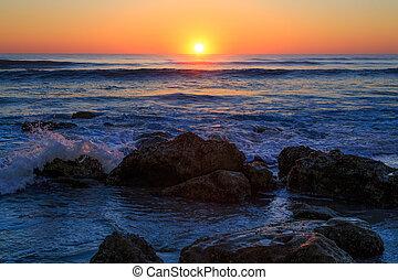 Amanecer en la playa rocosa
