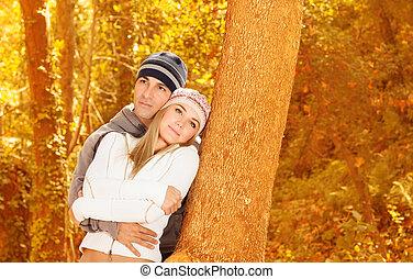 Amantes felices en el parque de otoño