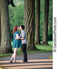 Amar a una pareja joven besándose en el parque
