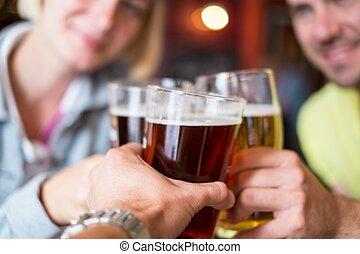 Amigos con cerveza brindando en un pub