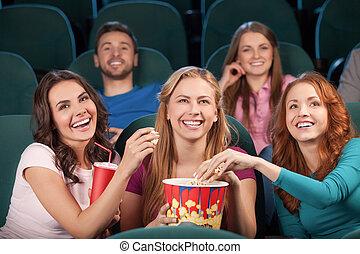 Amigos en el cine. Los jóvenes felices viendo películas en el cine y riéndose