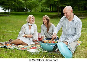 Amigos en el parque comiendo picnic BBQ
