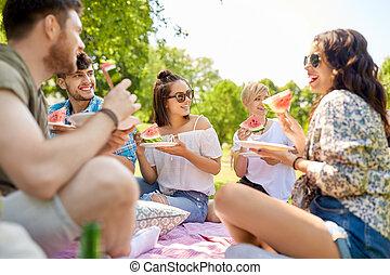 Amigos felices comiendo sandía en el picnic de verano